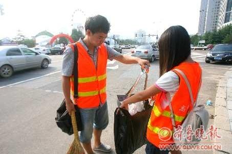 17日,在啤酒城外,来自青岛科技大学的志愿者张璐和崔立文正在打扫