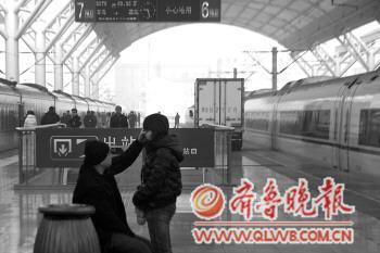 16日,在青岛火车站,一名男子为女孩擦去脸上的泪水,即将离别,难舍