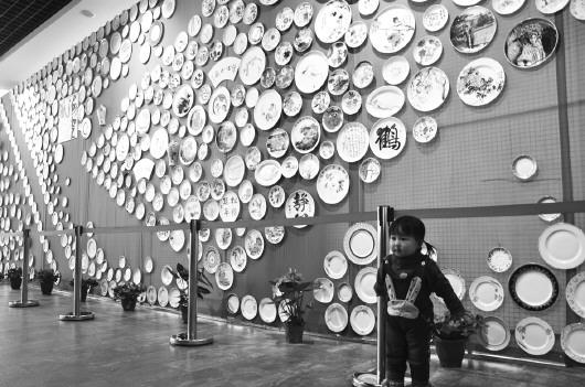 一名孩子在市博物馆内手绘看盘文化墙前面摆出照相